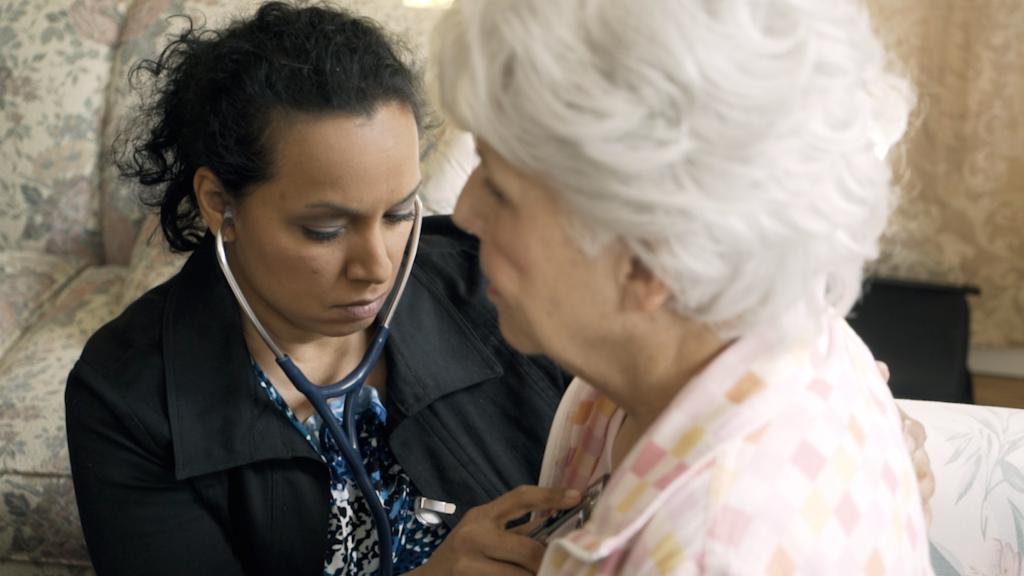 Nurse Practitioner listening on stethescope